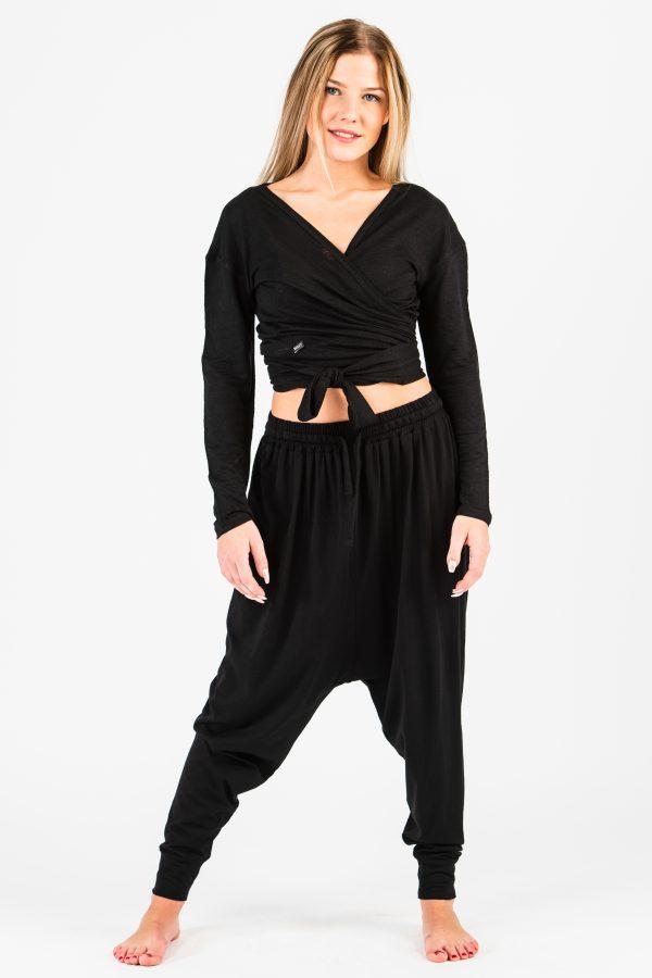 Modellen bär en omlott-tröja i svart linne-trikå och svarta haremsbyxor.