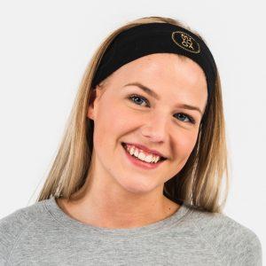 Modellen bär ett svart hårband med loggan i guld.