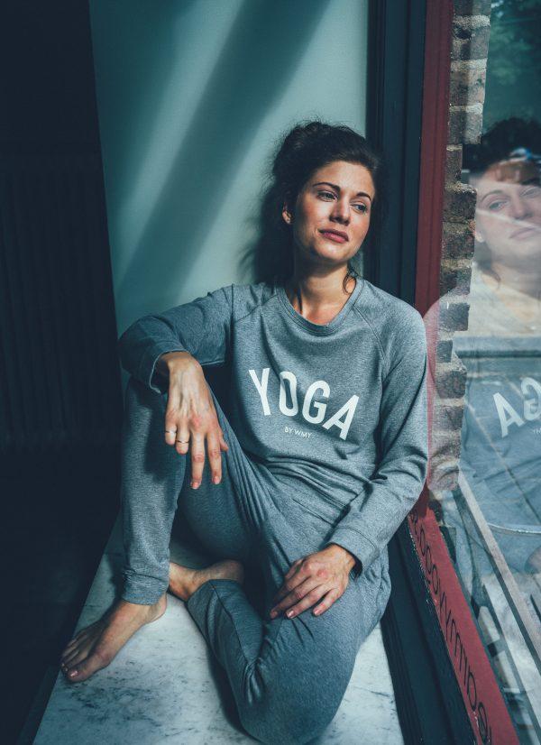 Modell i grå yogatröja med texten YOGA i vit tillsammans med grå yogabyxor.