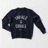 Yogatröja med Inhale & Exhale broderat på en sweatshirt i marinblått.
