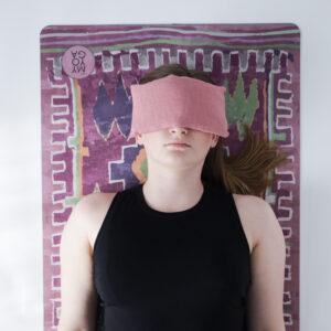 Boho-mönstrad yoga matta i lila toner och mörkt rosa ögonkudde i linne.