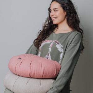 Modell som bär på en massa meditationskuddar i linne.