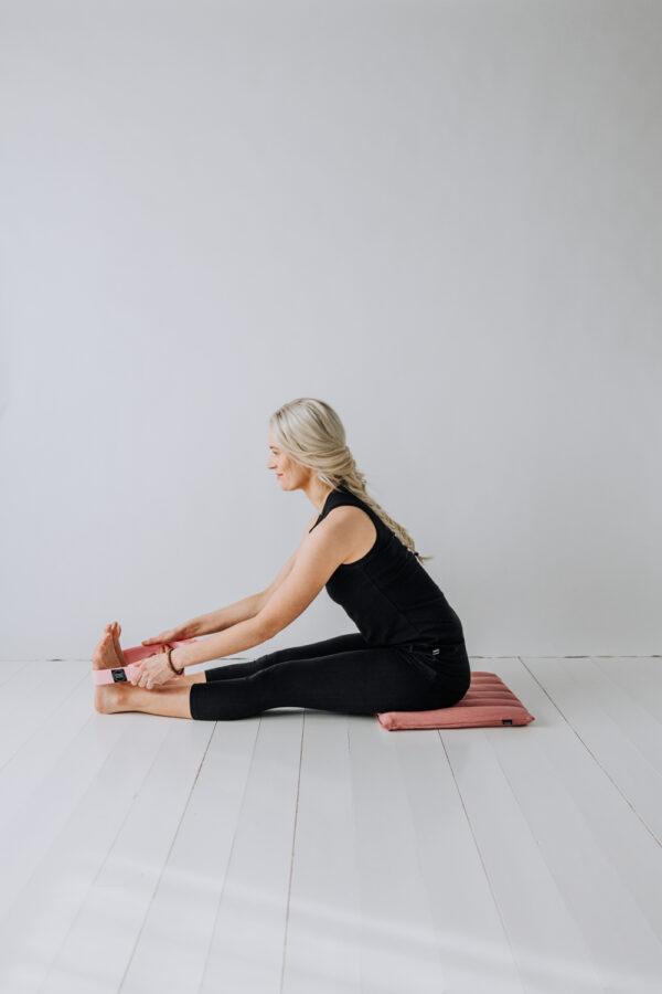 Yogi sittandes på en liten meditationsmatta användandes ett yoga bälte.