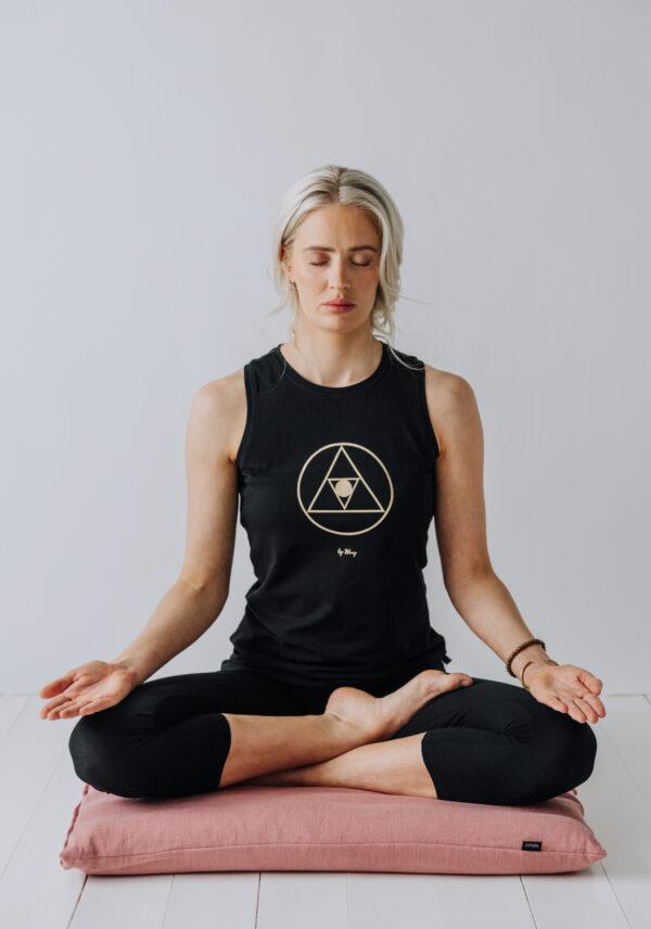 Mediterande Yogi sittandes på en Zabuton, stor meditations matta, i linne.
