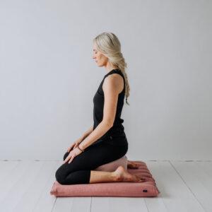 Mediterande Yogi sittandes på både en meditations kudde och en Zabuton, stor meditations matta, i linne