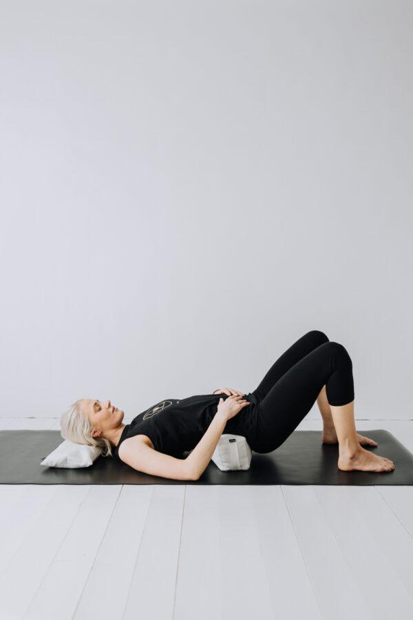 Yoga med nacken vilandes på en liten kudde och ett litet resebolster i svanken.