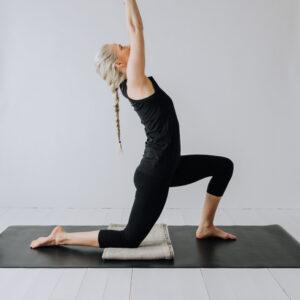 Yogi i low lunge pose med knät på en linnefilt.