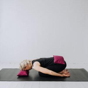 Yogi i barnets position med pannan vilandes på en udde 20*40 i linne och en tyngdkudde på svanken.