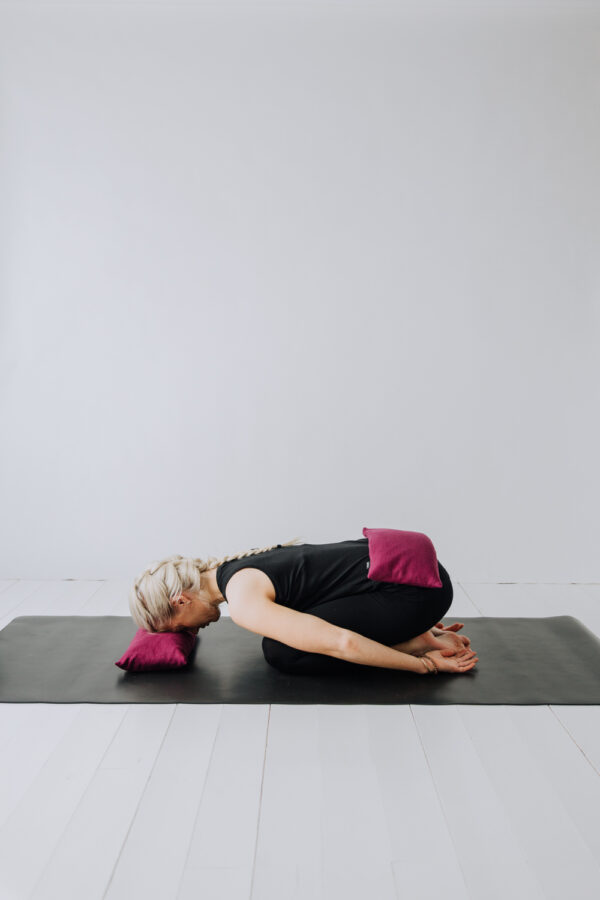 Yogi i barnets position med pannan vilandes på en liten kudde och en tyngdkudde på svanken.