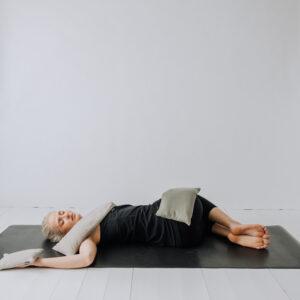 Yogi liggandes i en twist med tyngdkuddar på axeln, höften och handflatan.