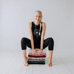 Yogi sittandes på en hög med små meditationsmattor - mini-zabuton