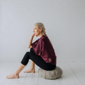 Yogi sittandes på en meditationskudde, zafu, med en sjal över axlarna.